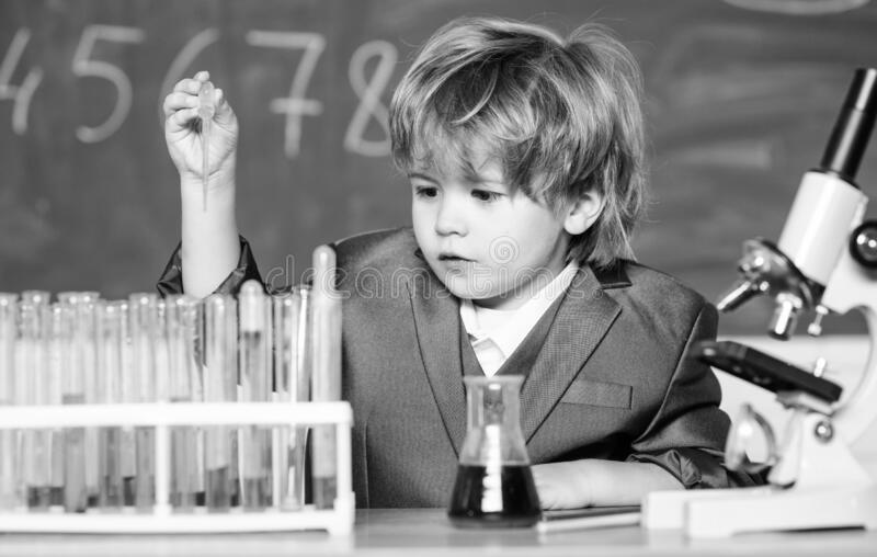 Explore biological molecules. Toddler genius baby. Boy near microscope and test tubes in school classroom. Technology. And science concept. Kid study biology royalty free stock photo