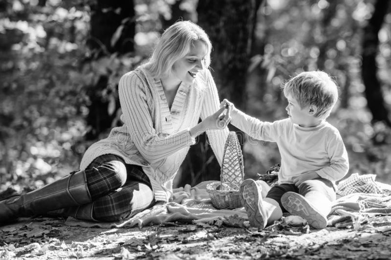 Explore nature together. Mom and kid boy relaxing while hiking in forest. Family picnic. Mother pretty woman and little. Son sit on plaid relaxing forest picnic royalty free stock image
