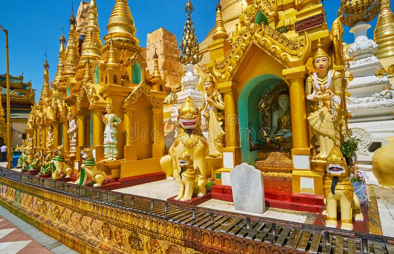 The intricate decors of Shwedagon outer stupas, Yangon, Myanmar. Explore the small outer stupas of Shwedagon Zedi Daw with Nat statues and mythic creatures royalty free stock image