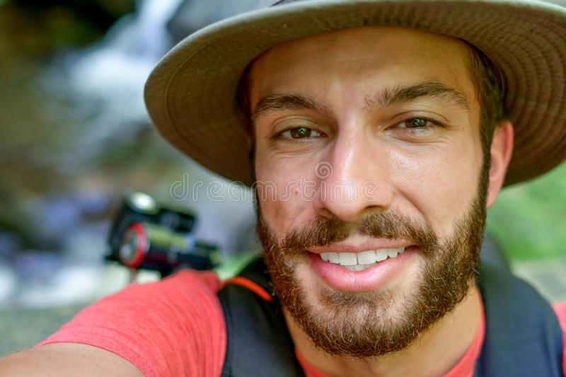 Explorer takes a selfie while in his element. Which leaves him smiling with joy. Wearing his adventure hat and throwing his tripod over his shoulder to hike royalty free stock photos