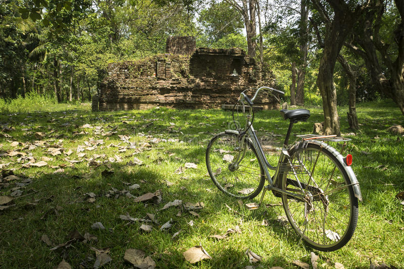 Exploring ancient temples by bike, Anuradhapura, Sri Lanka. Bike in fron of an ancient temple in the jungle stock photography