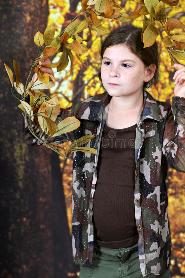 Exploring the Autumn Woods. A pretty elementary girl in an autumn woods, looking out between low branches royalty free stock photos