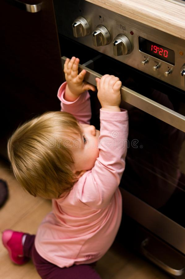 Toddler gripping kitchen oven door royalty free stock image
