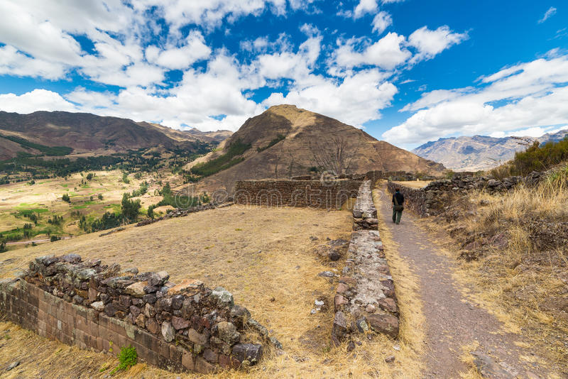 Exploring Inca Trails and ruins of Pisac, Peru. Tourist exploring the Inca Trails leading to the ruins of Pisac, Sacred Valley, major travel destination in Cusco royalty free stock photo