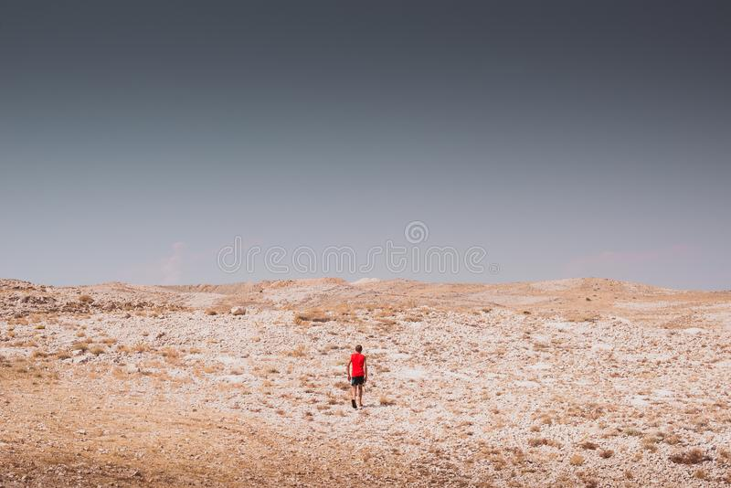Exploring - lonely boy walking in a rocky desert freedom and adventure lifestyle and sport concepts stock photo
