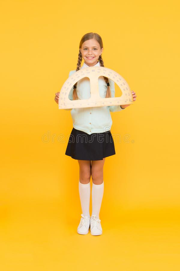 Exploring the properties of protractor in the lesson. Cute girl holding protractor for lesson in maths. Little child at royalty free stock photography