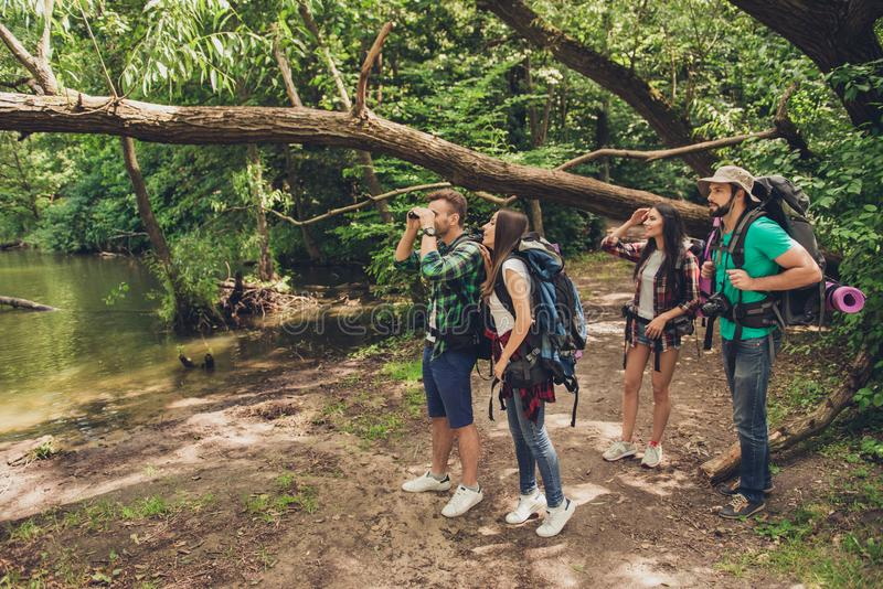 Exploring, researches and expedition concept. Four tourists are hiking near the river in a wild spring wood, guy is looking in the royalty free stock photo