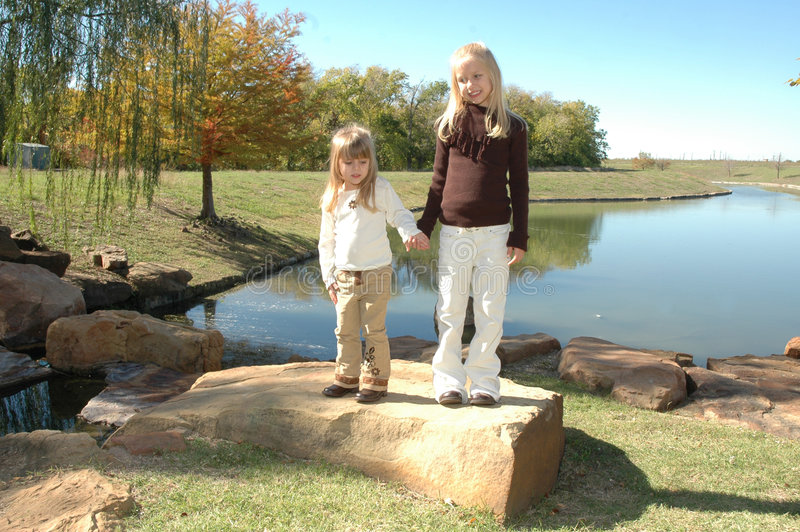 Exploring Sisters. Two beautiful little blond sisters play and explore a nature area in a park. Spending time with family and being together. Two little girls royalty free stock photo
