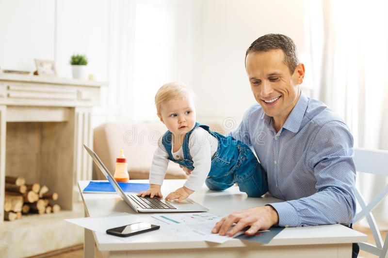 Lovely baby touching a laptop on the table while helping his father. Exploring technologies. Cute pretty baby crawling on the table and touching a modern laptop stock photo