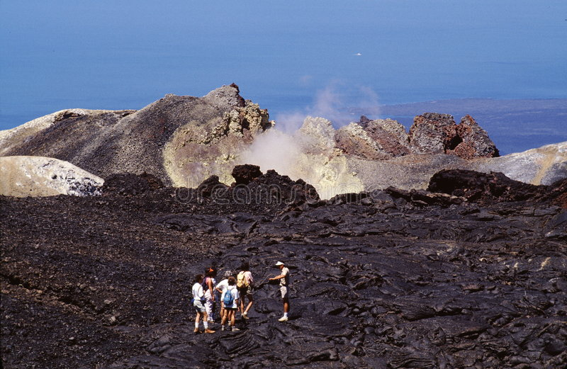 Exploring a volcano. A view of hikers on a ranger-guided hike of the Sierra Negra Volcano on Isabela Island in the Galapagos of Ecuador stock photography