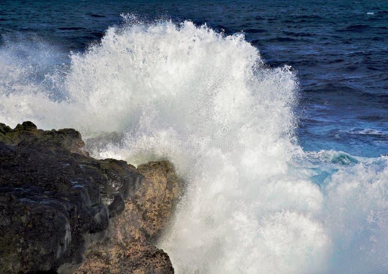 Explosão da onda do mar em rochas no oceano imagem de stock