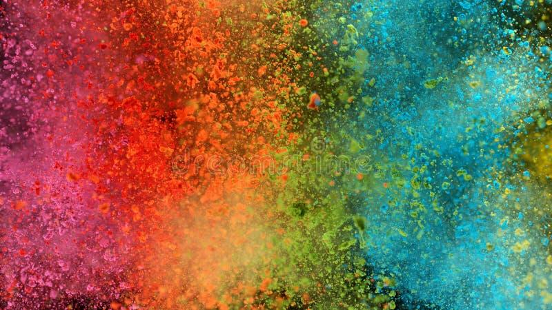 Explosão de pó colorido isolado sobre fundo negro imagem de stock