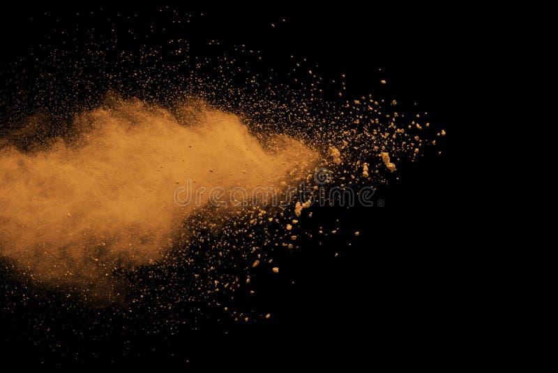 Explosão de poeira alaranjada abstrata no fundo preto fotografia de stock royalty free