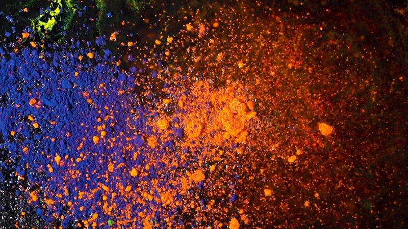 Explosão de poeira colorida brilhante em um fundo preto, conceito da arte Movimento de tintas azuis e alaranjadas do pó, colorido fotografia de stock
