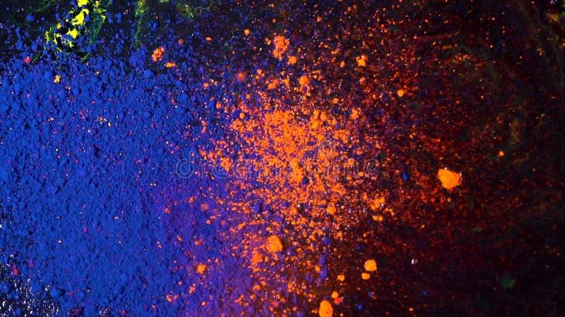 Explosão de poeira colorida brilhante em um fundo preto, conceito da arte Movimento de tintas azuis e alaranjadas do pó, colorido imagem de stock