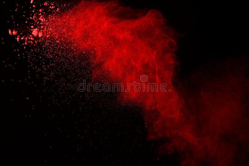 Explosão do pó vermelho no fundo preto Sumário da poeira colorida splatted foto de stock