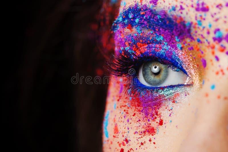 Explosión del color, sombras multicoloras dispersadas en los párpados Ojos coloreados de Smokey y cejas azules imágenes de archivo libres de regalías