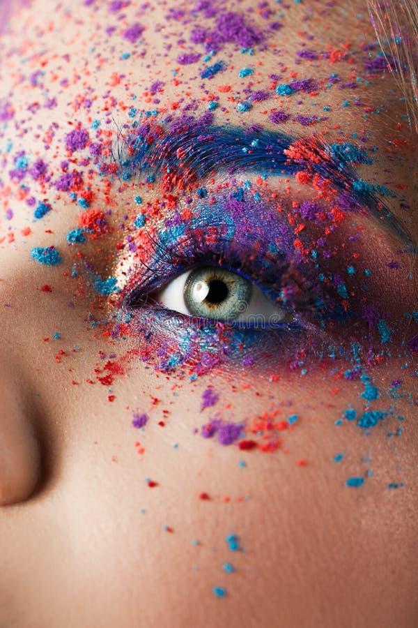Explosión del color, sombras multicoloras dispersadas en los párpados Ojos coloreados de Smokey y cejas azules fotos de archivo