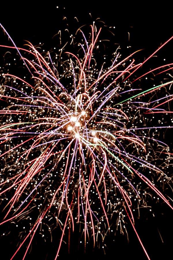 Explosie van vuurwerk tegen de achtergrond van de nachthemel Multi-colored lijnen en de vonken zijn zichtbaar stock foto