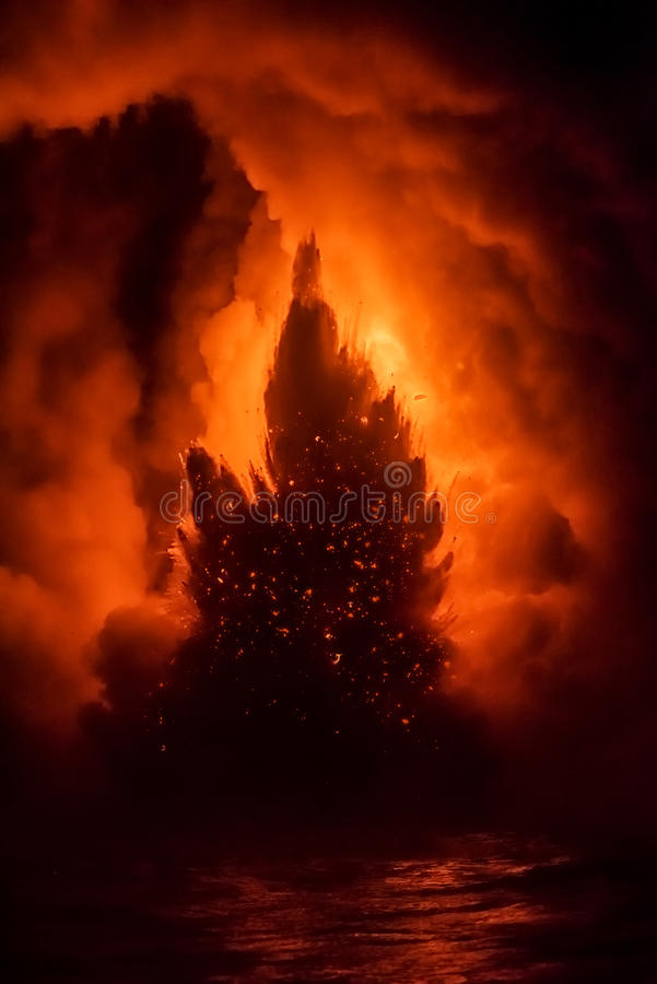 Explosing lava in Hawaii. A lava flow on the big Island of Hawaii known as the fire hose spews out molten magma from Kilauea Volcano into the ocean, causing royalty free stock photo