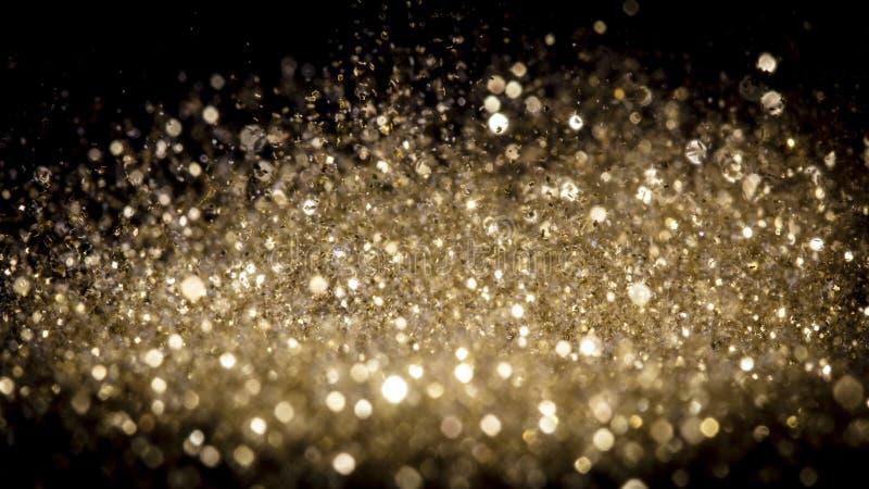 Explosion av mousserande guldstoft mot svart bakgrund royaltyfri foto