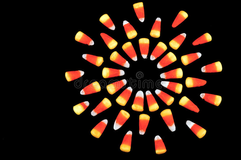 Explosion of Candy Corn. Overhead closeup of a group of candy corn arranged to resemble a representation of the sun against a black background royalty free stock photos