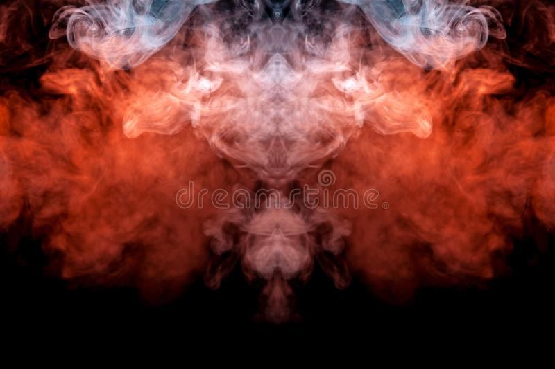 The explosion of fiery clouds of orange smoke on a black background jet of scattering steam from the vape flames royalty free stock images