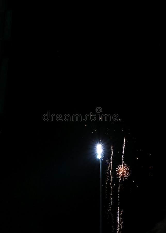 Explosion of fireworks alongside night lights of football game royalty free stock image