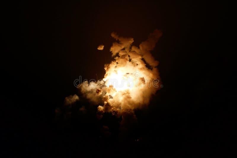 Explosion lighting up night sky with smoke stock photos