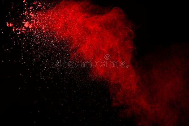 Explosion of red powder on black background. Abstract of colored dust splatted. stock photo