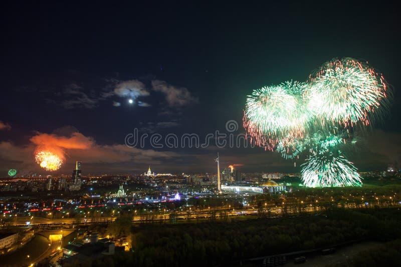 Explosiones brillantes de los fuegos artificiales en cielo nocturno en Moscú, Rusia fotos de archivo