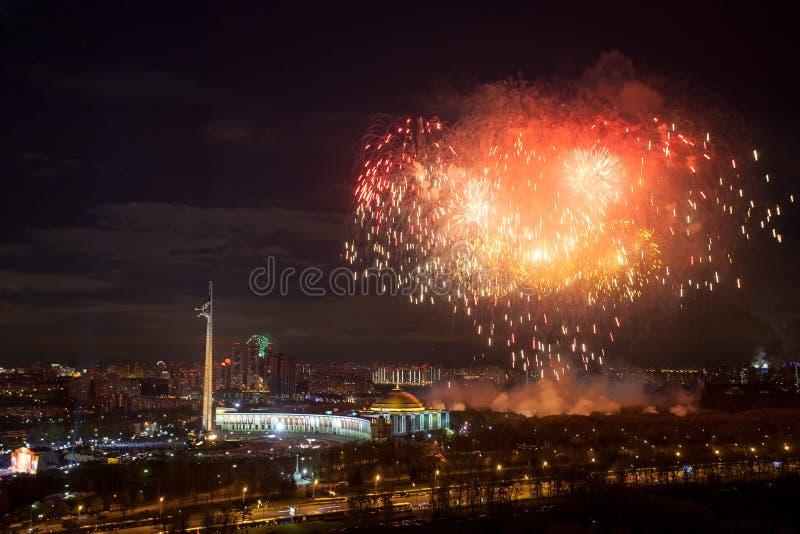 Explosiones brillantes de los fuegos artificiales en cielo nocturno en Moscú, Rusia imagen de archivo