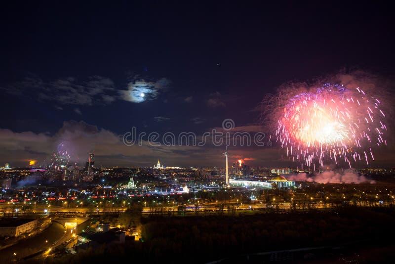 Explosiones brillantes de los fuegos artificiales en cielo nocturno en Moscú, Rusia fotografía de archivo