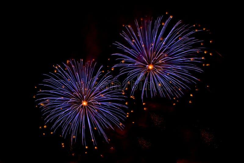 Explosiones de fuegos artificiales azules y anaranjados fotos de archivo