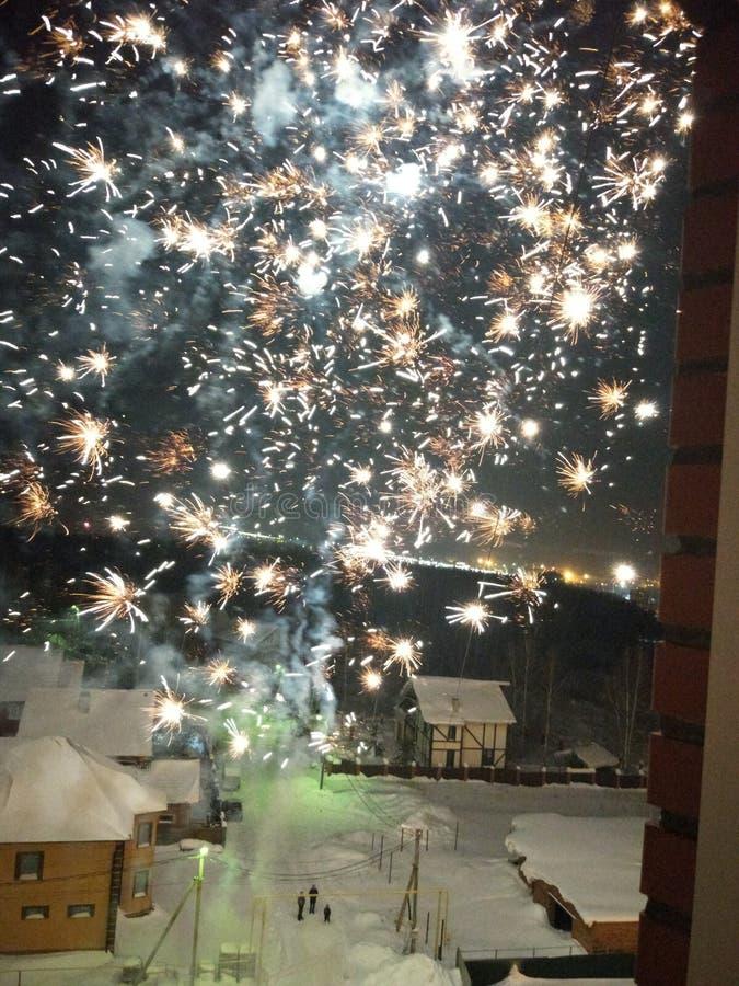 Explosiones de los fuegos artificiales a trav?s de la ventana abierta en una noche del invierno fotos de archivo