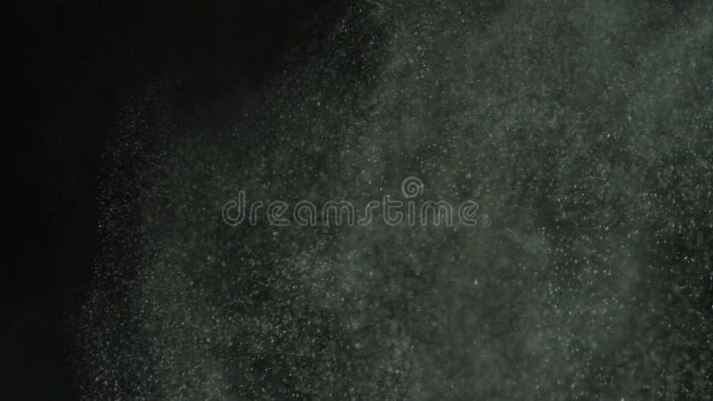 Explosiones del polvo blanco en fondo negro Cantidad com?n Corrientes de la explosi?n del polvo blanco en fondo aislado negro imagenes de archivo