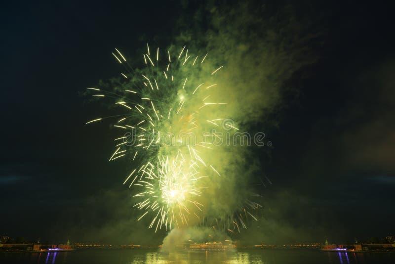 Explosions-Grünfeuerwerke des Nachtstadthimmels helle über Fluss stockbild