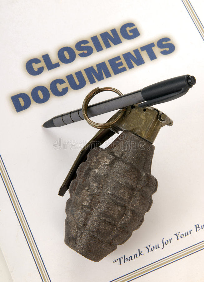 Explosive Loan. A hand grenade rigged to blow up when loan documents are signed royalty free stock image