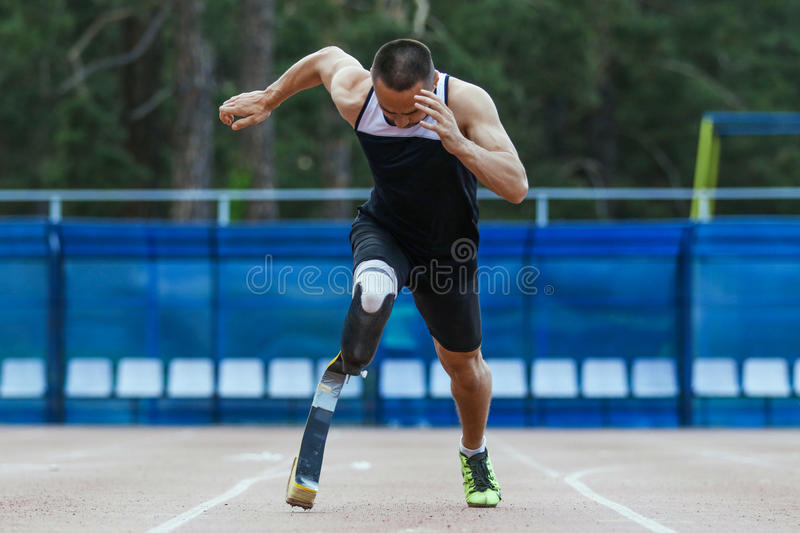 Explosive start of athlete with handicap. At the stadium royalty free stock images