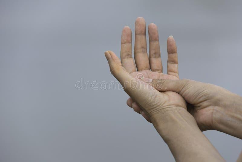 Explotación agrícola de la mujer su mano Dolor en una mano de la mujer Mano dolorosa de masaje femenina para el concepto doloroso imágenes de archivo libres de regalías