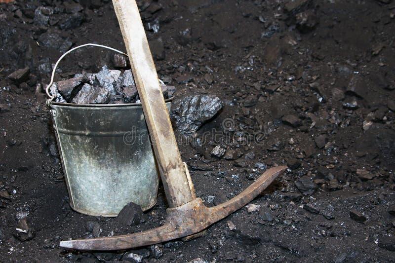Explotación del cabón retra Piqueta y el cubo con el carbón en los míos imágenes de archivo libres de regalías