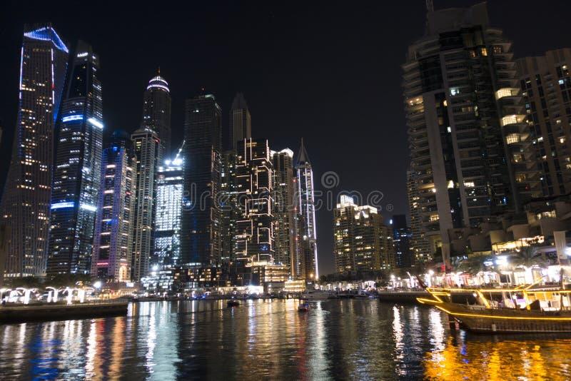 Exponerade skyskrapor från den Dubai marina reflekterade i vatten under natten arkivfoto