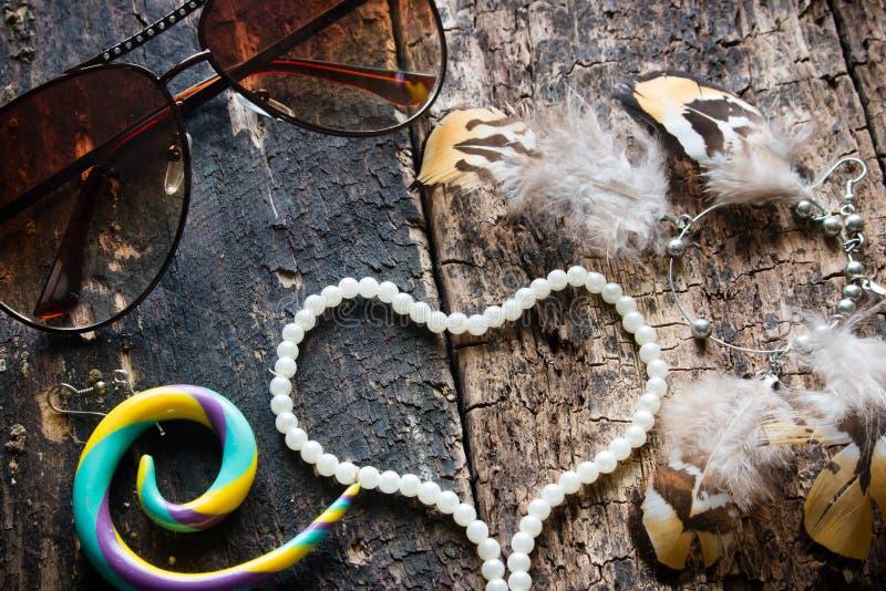Exponeringsglas örhängen med fjädrar, Dreamcatcher, smycken, pryder med pärlor i formen av en hjärta på ett trä royaltyfri foto