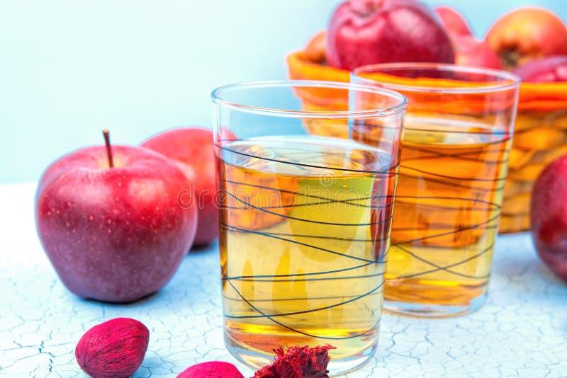 Exponeringsglas av äppelmust och röda äpplen på en blå gammal träbackg royaltyfri bild