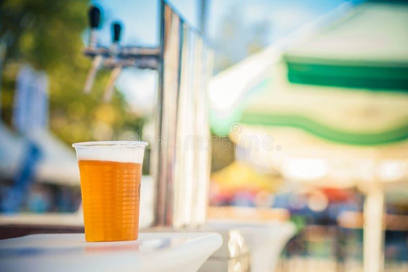 Exponeringsglas av öl i en plast- kopp fotografering för bildbyråer