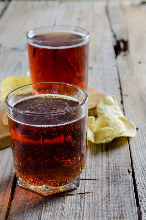 Exponeringsglas av öl med chiper på en träbakgrund royaltyfria foton