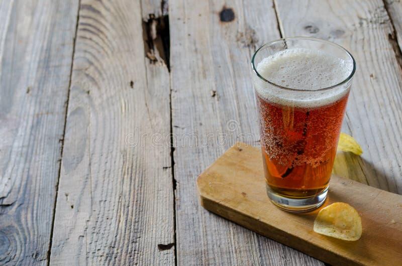 Exponeringsglas av öl med chiper på en träbakgrund arkivfoton