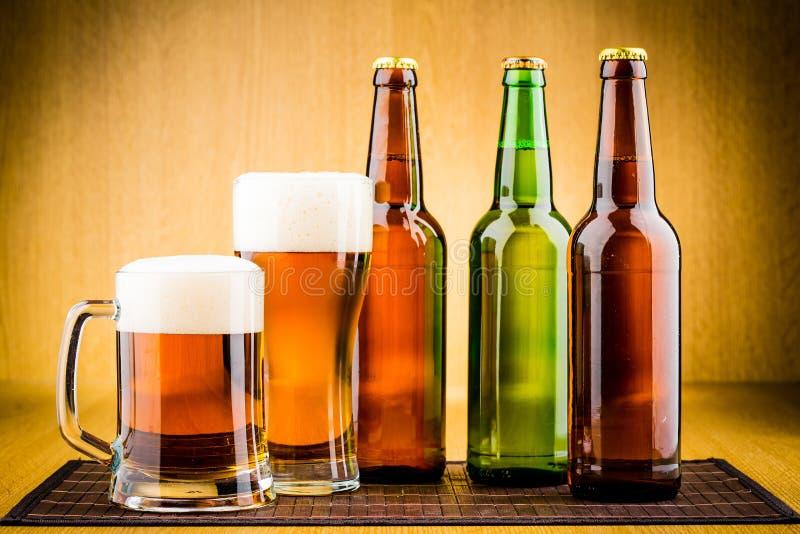Exponeringsglas av öl med flaskor arkivfoto