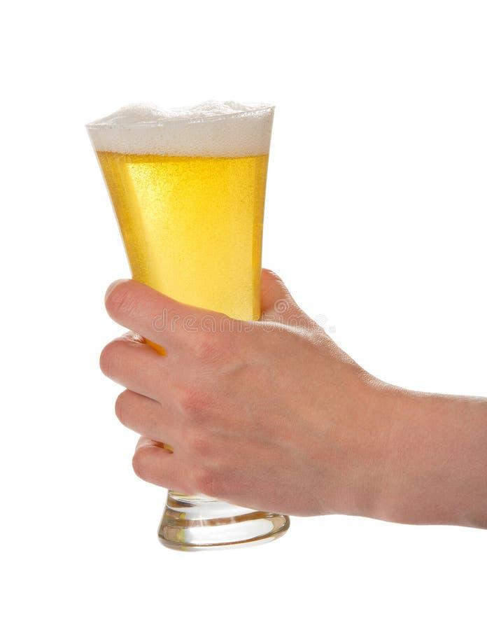 Exponeringsglas av öl med skum och små medicinflaskor i hand royaltyfria foton