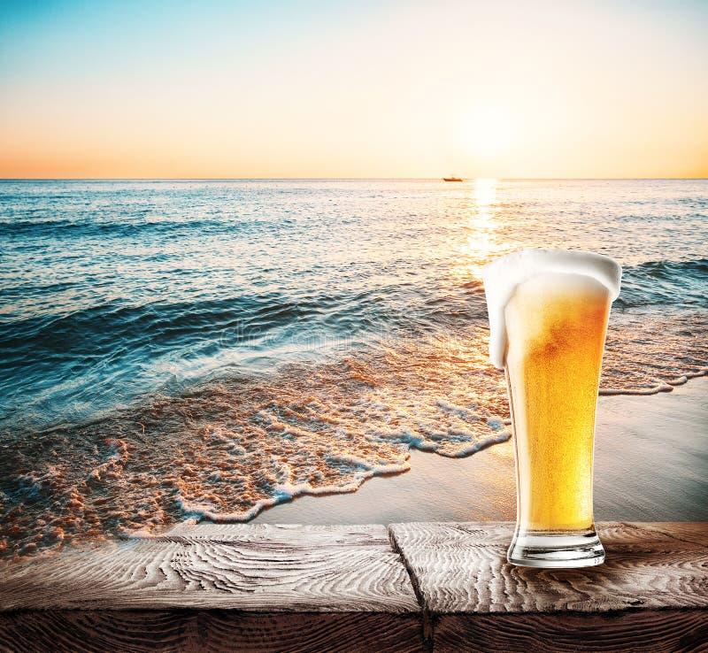 Exponeringsglas av öl med skum på en tabell royaltyfri fotografi